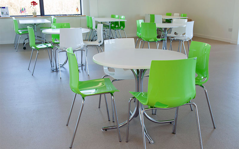 Green chairs at round white tables